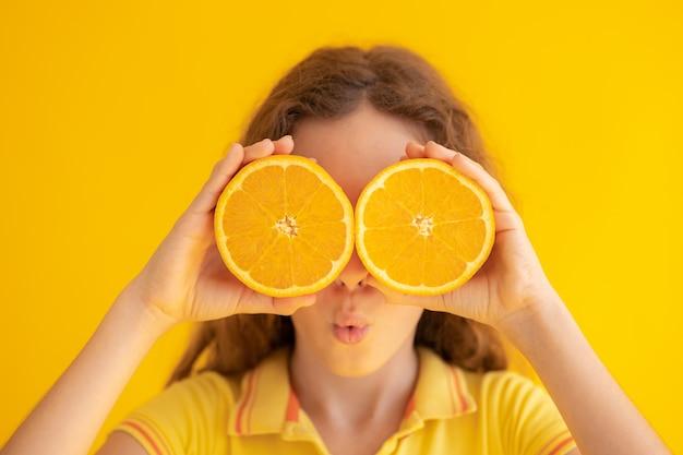 Bambino che tiene le metà arancioni invece degli occhiali da sole.