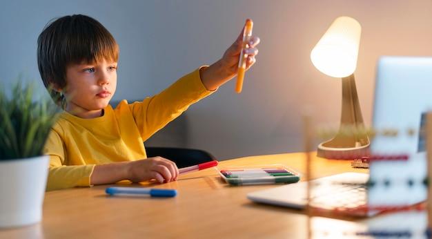 Bambino che tiene in mano un pennarello arancione
