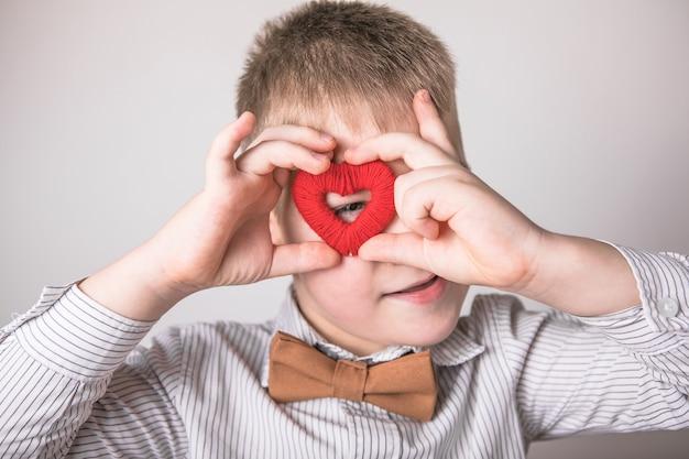 Bambino che tiene un piccolo cuore rosso
