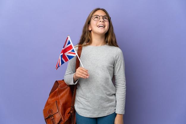 Bambino in possesso di una bandiera del regno unito su sfondo isolato ridendo