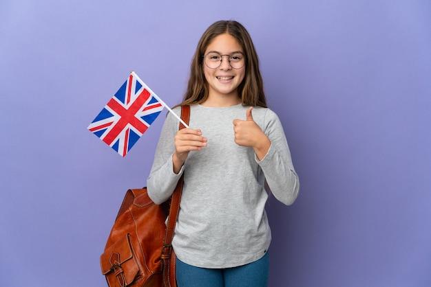 Il bambino che tiene una bandiera del regno unito sopra la parete isolata che dà un pollice aumenta il gesto