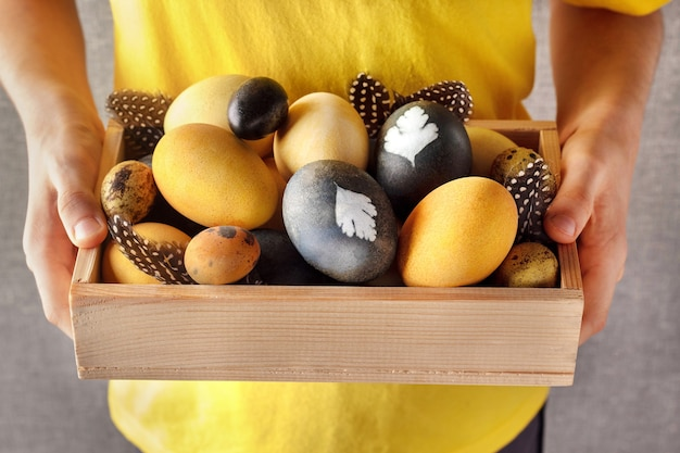 Bambino che tiene cassa di legno con uova di pasqua tinte naturalmente su sfondo grigio.