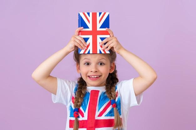 Il bambino tiene un libro di testo inglese sopra la sua testa ed è felice.