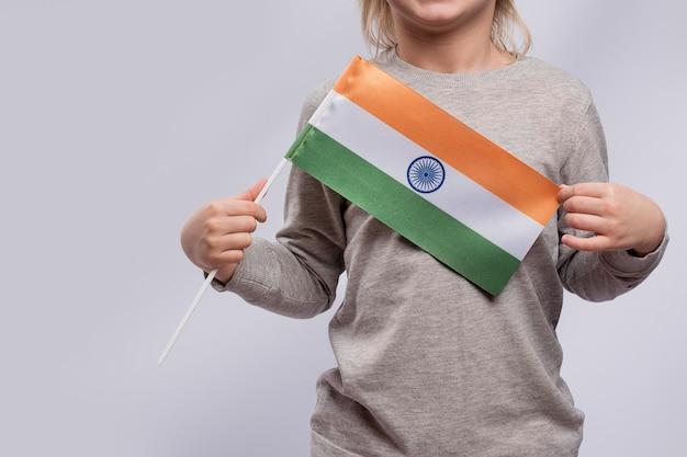 Il bambino tiene la bandiera dell'india. avvicinamento. visitare l'india con i bambini.