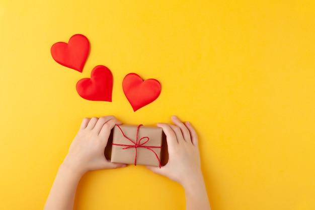 Il bambino tiene in mano la confezione regalo a sorpresa, molti cuori rossi, l'amore e il concetto di san valentino, orizzontale, parete gialla, spazio copia, vista dall'alto