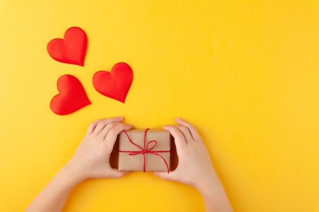 Il bambino tiene in mano la confezione regalo a sorpresa, molti cuori rossi, l'amore e il concetto di san valentino