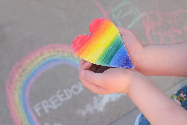 Il bambino tiene tra le mani un cuore di carta dipinto nei colori dell'arcobaleno dell'arcobaleno della comunità lgbt, gesso sul marciapiede, concetto di orgoglio del mese - arte temporanea