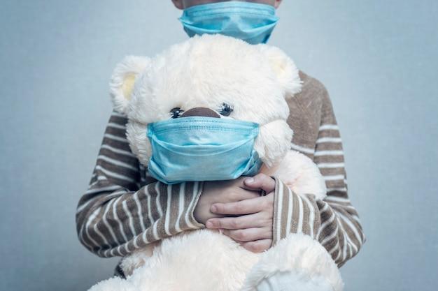 Un bambino tiene il suo orsacchiotto entrambi indossando maschere mediche protettive