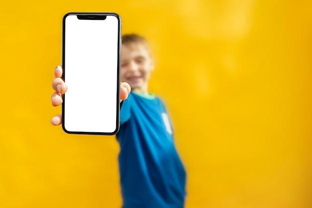 Il bambino tiene il telefono in mano per fare pubblicità su uno sfondo giallo. colore