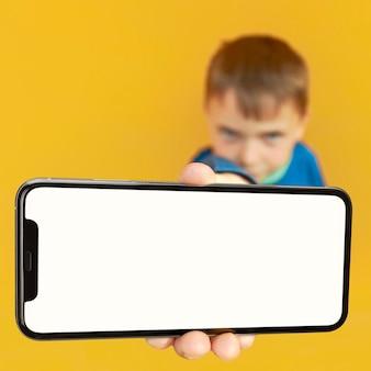 Il bambino tiene il telefono in mano per fare pubblicità su una superficie gialla. colore