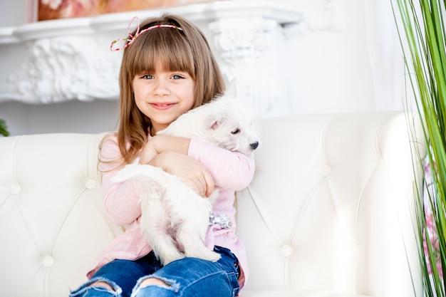 Il bambino abbraccia un cucciolo di terrier bianco