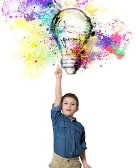 Il bambino indica una grande lampadina colorata progettata