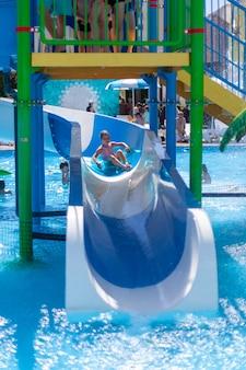 Un bambino su un cerchio gonfiabile cavalca uno scivolo d'acqua in un parco acquatico vacanze estive attive