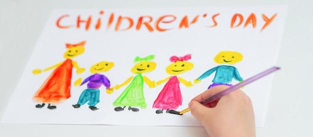 Il bambino sta disegnando il giorno dei bambini felici.