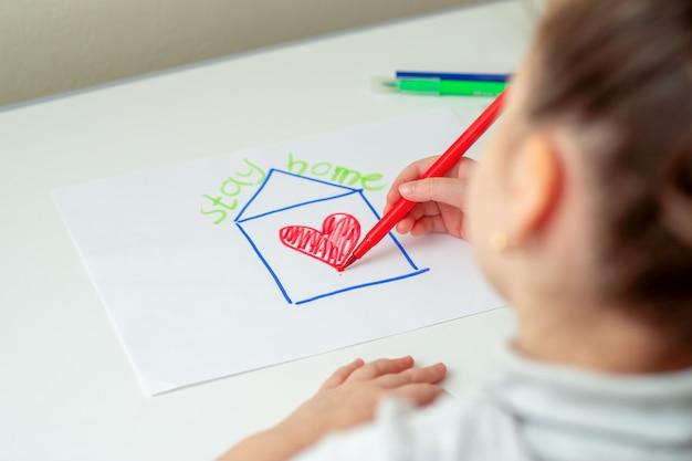 Il bambino sta disegnando casa con il cuore