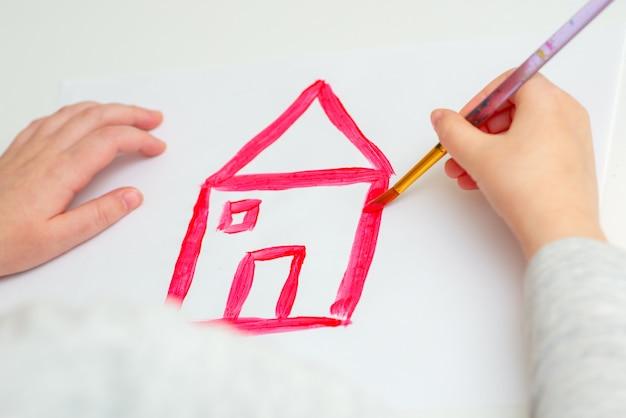 Il bambino sta disegnando casa