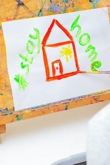 Il bambino sta disegnando la casa rossa con le parole resta a casa.