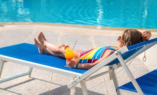 Il bambino sta bevendo un cocktail a bordo piscina