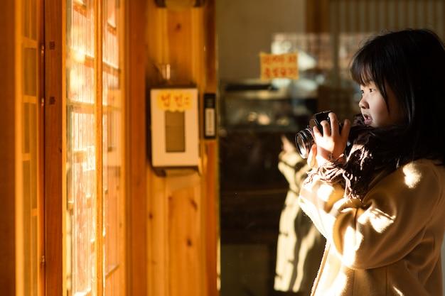 Il bambino tiene in mano la telecamera e guarda la finestra da cui entra la luce.