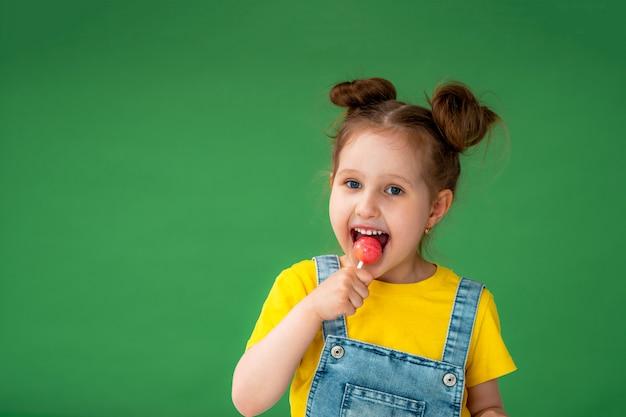 Il bambino sta tenendo una lecca-lecca che sorride distoglie lo sguardo, posando