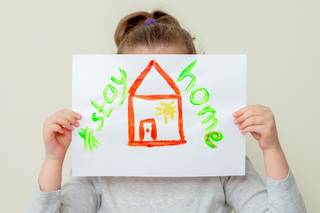 Il bambino tiene in mano una foto di casa