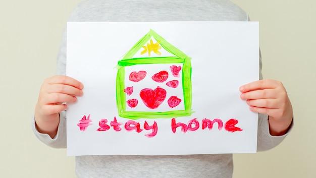 Il bambino tiene in mano un'immagine della casa.