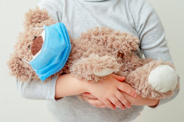Il bambino sta tenendo l'orso giocattolo in maschera medica.
