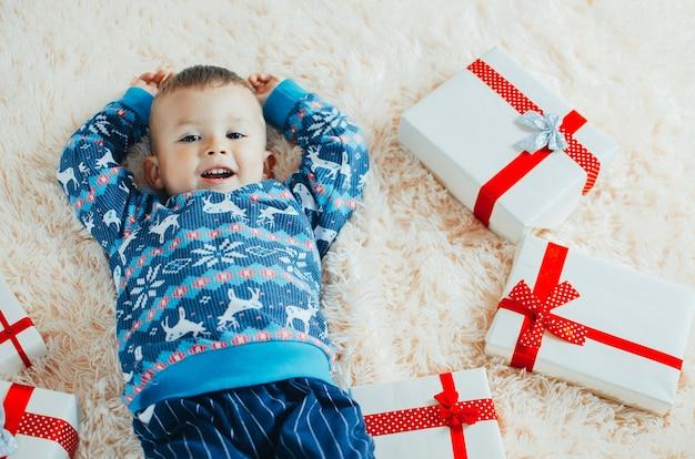 Il bambino è sdraiato sulla soffice coperta soffice, accanto a lui un mucchio di regali, il bambino è molto felice