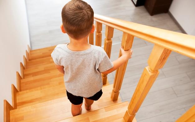 Il bambino si sta muovendo giù attraverso le scale di legno in casa
