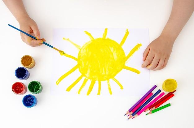 Il bambino sta dipingendo un quadro.
