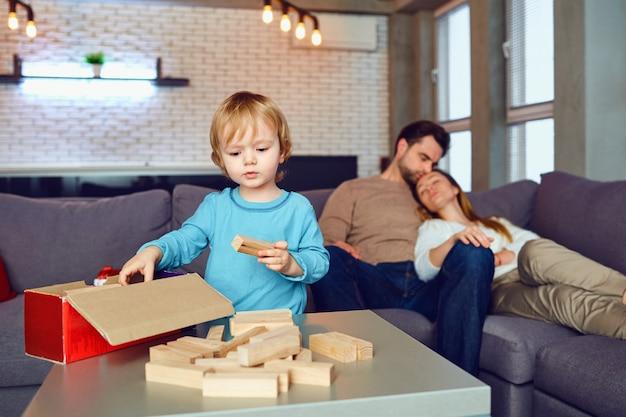Il bambino sta giocando a giochi da tavolo a casa. la famiglia felice sta riposando nel loro tempo libero nella stanza.