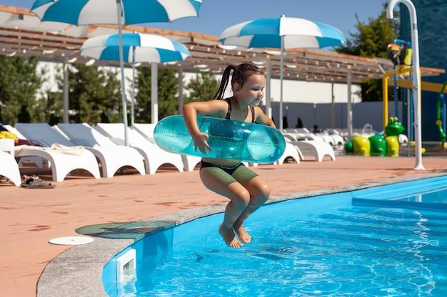 Il bambino sta giocando nel parco acquatico la bambina salta in un anello gonfiabile in piscina con sedie a sdraio...