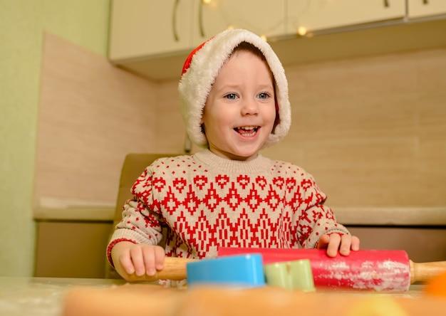 Il bambino sta preparando i biscotti di natale