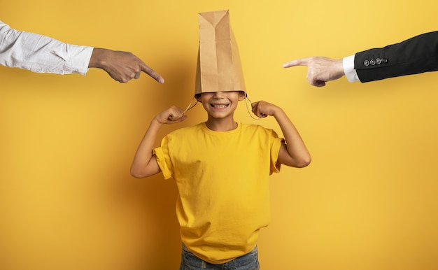 Il bambino viene rimproverato e nasconde la testa in una borsa della spesa