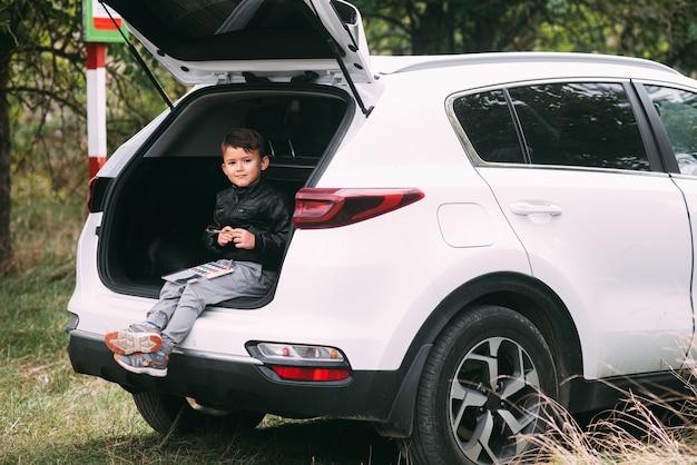 Un bambino è seduto nel bagagliaio di un'auto suv o crossover con guazzo dipinge un'auto in autunno per...