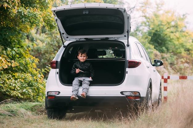 Un bambino è seduto nel bagagliaio di un'auto suv o crossover con vernici a guazzo, un'auto nella foresta autunnale