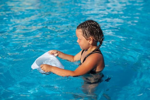 Bambino è in piedi in piscina piccola ragazza abbronzata con trecce intrecciate sulla testa bagnando panama bianco h...