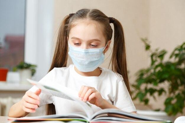 Il bambino studia a casa, studia a casa durante la quarantena, bambino mascherato che studia a casa