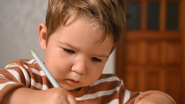 Il bambino scrive con concentrazione.