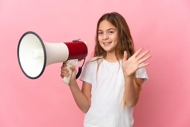 Bambino sopra fondo rosa isolato che tiene un megafono e che saluta con la mano con l'espressione felice
