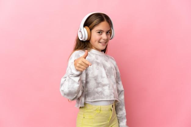 Bambino su sfondo rosa isolato che ascolta musica
