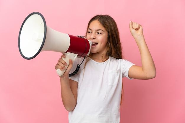 Bambino su sfondo rosa isolato che grida tramite un megafono per annunciare qualcosa in posizione laterale