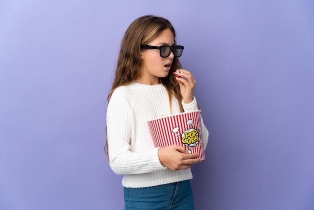 Bambino sopra la parete viola isolata con gli occhiali 3d e che tiene un grande secchio di popcorn mentre guarda di lato