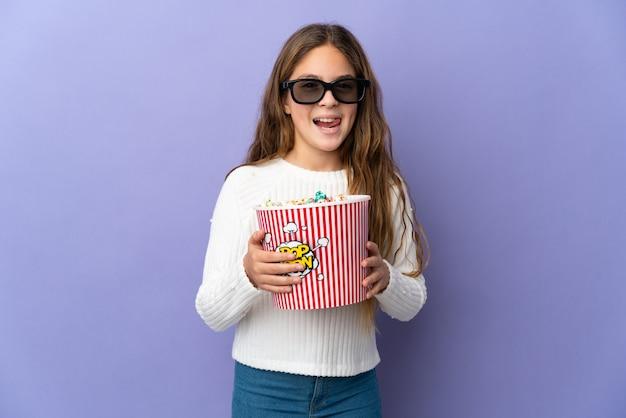 Bambino sopra la parete viola isolata con gli occhiali 3d e che tiene un grande secchio di popcorn