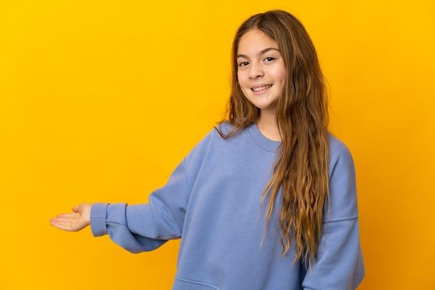 Bambino su sfondo giallo isolato che allunga le mani di lato per invitare a venire