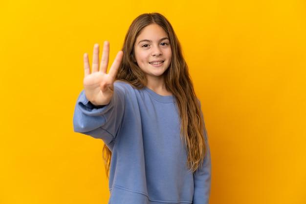 Bambino sopra la parete gialla isolata felice e che conta quattro con le dita