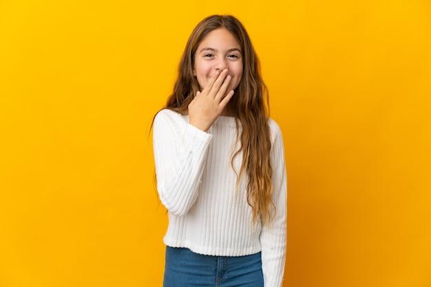 Bambino sopra la parete gialla isolata felice e sorridente che copre la bocca con la mano