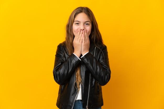 Bambino sopra la parete gialla isolata felice e sorridente che copre la bocca con le mani