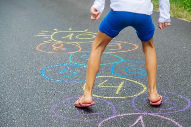 Bambino che salta classici sul marciapiede. messa a fuoco selettiva.