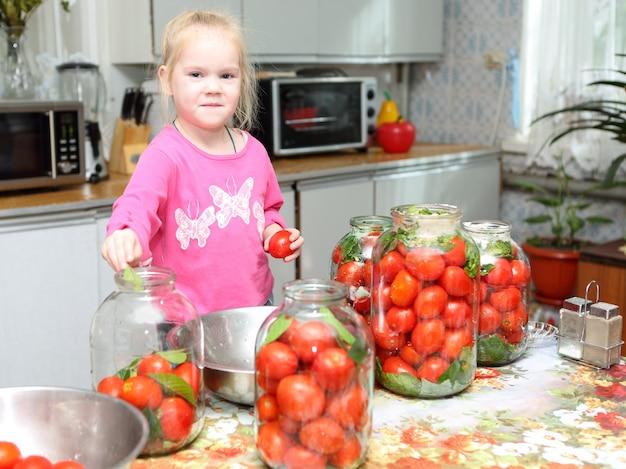 Bambino in cucina che prepara pomodori in scatola